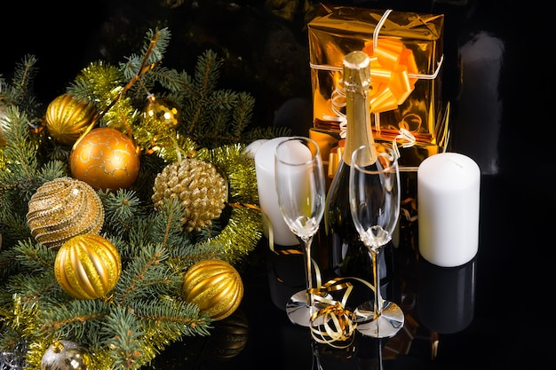 お祝いの静物のハイアングルビュー-ギフト、キャンドル、クリスマスボールと見掛け倒しの装飾された常緑樹と黒の背景にエレガントなグラスとシャンパンのボトル