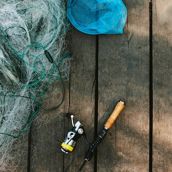 High angle view of fishing rod and net on wooden plank
