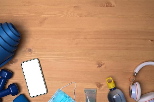 Высокий угол обзора фитнес-оборудования и смартфона на деревянных фоне.