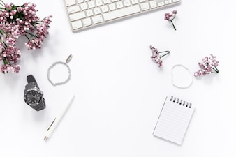 High angle view of flower; bracelet; wrist watch; pen; spiral notepad; and keyboard on white background