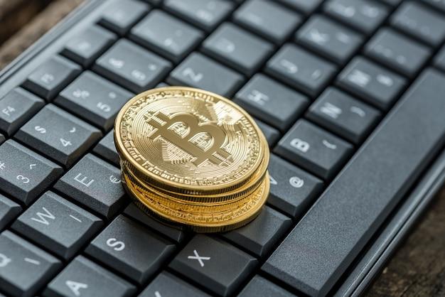 디지털 수입 및 통화에 대한 개념으로 키보드에 있는 4개의 황금 비트코인의 높은 각도 보기.