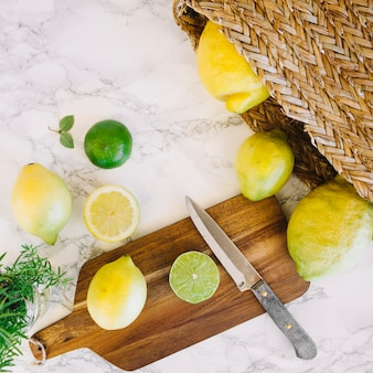 High angle view of fresh lemon and knife on chopping board