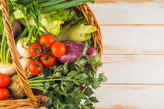 High angle view of fresh organic vegetables in wicker basket on wooden surface