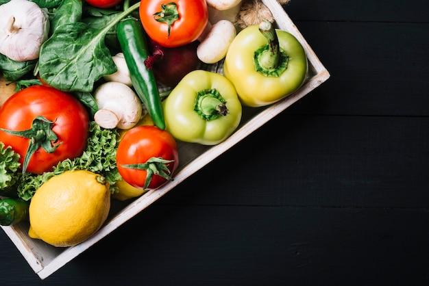 Высокий угол обзора свежих овощей в контейнере на черном фоне