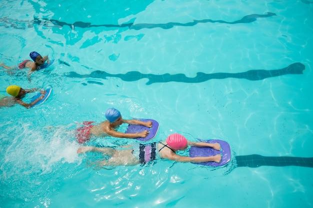 수영장에서 수영하는 동안 킥보드를 사용하는 소녀와 소년의 높은 각도보기