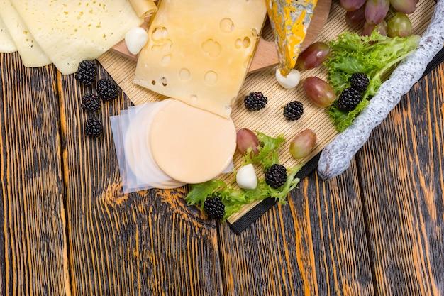 Высокий угол обзора сырной доски для гурманов с разнообразными сырами, украшенной свежими фруктами, подается на деревенском деревянном столе с копией пространства