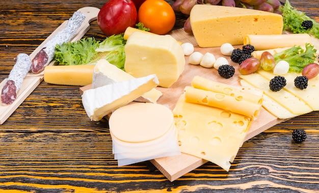 さまざまなチーズ、硬化肉、新鮮なフルーツを木目とコピースペースのある素朴な木製テーブルで提供するグルメチーズボードのハイアングルビュー
