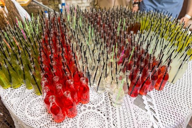 Высокий угол обзора изысканных газированных напитков в прозрачных стеклянных бутылках с трубочками для питья, упорядоченными по цвету на столе на мероприятии