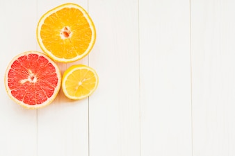 High angle view of halved citrus fruits on wooden background
