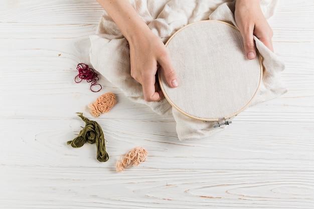 Взгляд высокого угла руки держа обруч с красочной резьбой над белым деревянным столом