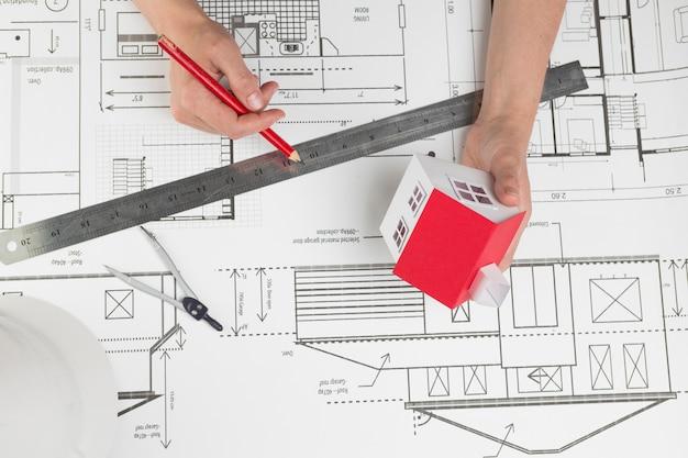 청사진을 통해 작은 집 모델과 연필을 들고 손의 높은 각도보기