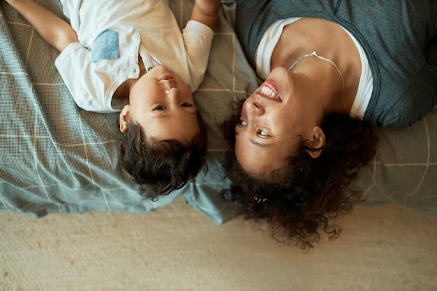 Высокий угол обзора счастливой красивой молодой женщины смешанной расы, лежащей на одеяле на полу вверх стороной вниз со своим очаровательным маленьким сыном, рассказывающей ему сказку