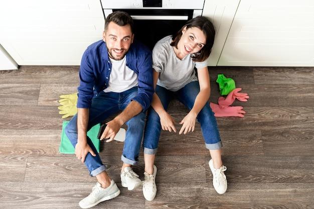 Высокий угол обзора счастливой беззаботной молодой пары в повседневной одежде, сидящей на полу в резиновых перчатках во время отдыха после уборки дома