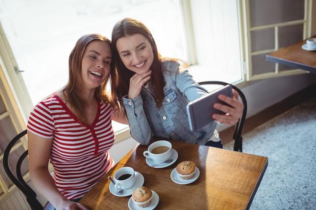 カフェでselfieを取って幸せな友達の高角度のビュー