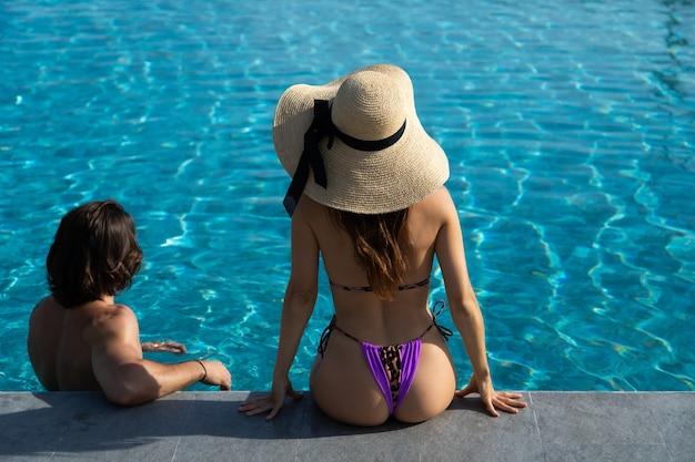 プールサイドで幸せな若いカップルのハイアングルビュー。カップルはプールパーティーでリラックスしています。夏休みのコンセプト