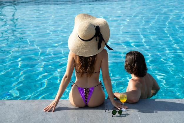 수영장에서 행복 한 젊은 커플의 높은 각도보기. 부부는 수영장 파티에서 편안합니다. 여름 휴가 개념