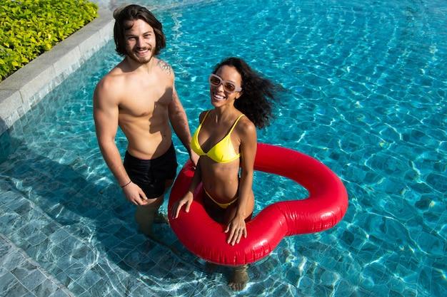 Высокий угол обзора счастливой молодой пары у бассейна. пара расслабляется на вечеринке у бассейна. концепция летних каникул