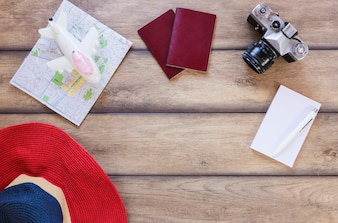 High angle view of hat; map; airplane; passport; camera; paper and pain on wooden surface