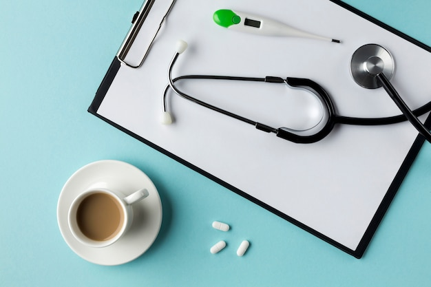 Взгляд высокого угла инструментов и лекарств здравоохранения около спирального блокнота и компьтер-книжки над столом