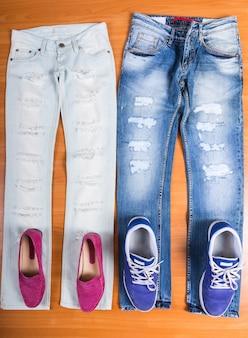 Высокий угол обзора его и ее рваных и потрепанных синих джинсов, разложенных на деревянной поверхности, с подходящей обувью - розовые лоферы и фиолетовые кроссовки