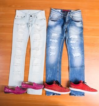Высокий угол обзора его и ее рваных и потрепанных синих джинсов, разложенных на деревянной поверхности, с подходящей обувью - стильные розовые лоферы и красные кроссовки