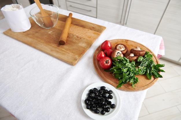 テーブルの上の木製のキッチンボード上のピザの材料の高角度ビュー。