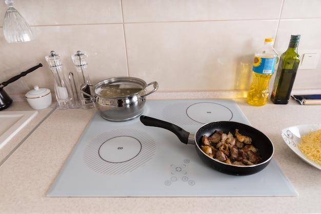 팬에 고기 튀김과 냄비에 끓는 파스타가 있는 주방 스토브 상단의 높은 각도 보기 - 카운터는 식사 준비를 위한 다른 재료로 흩어져 있습니다.