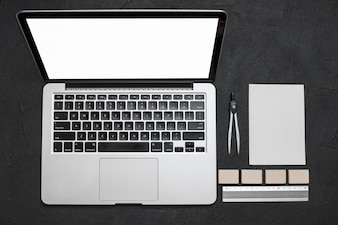 High angle view of laptop and stationeries on black background
