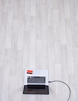 ラップトップの高角度のビューは、クレジットカードが付いている空の部屋の床にあります。