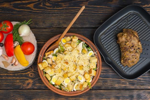 Вид под большим углом на большое глиняное блюдо с вкусным салатом цезарь