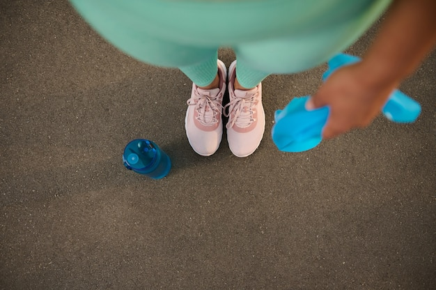 Высокий угол обзора ног подтянутой женщины в розовых кроссовках, держащей синюю резинку для фитнеса и стоящей на детской площадке рядом с бутылкой пресной воды