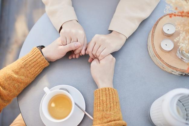 テーブルでお茶を飲みながら手をつないで愛するカップルの高角度のビュー