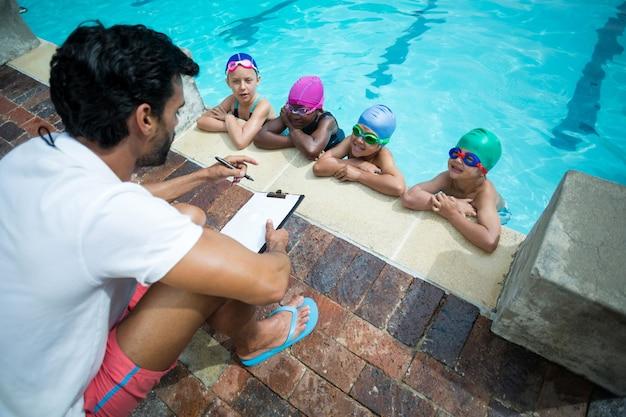 Pooldiseで小さなスイマーを説明するクリップボードを持つ男性インストラクターの高角度ビュー