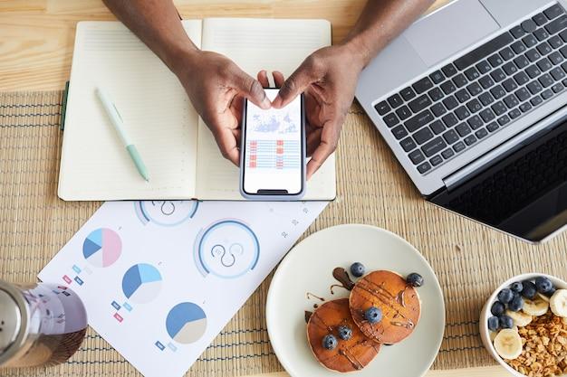 朝食時にテーブルで作業しながら彼の携帯電話でビジネスチャートを調べる男性の高角度ビュー