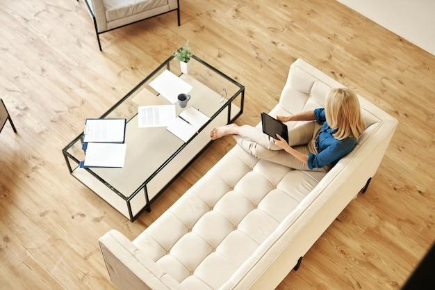 自宅で仕事をしながらタブレットpcを使用してカジュアルウェアで成熟した女性の高角度ビュー