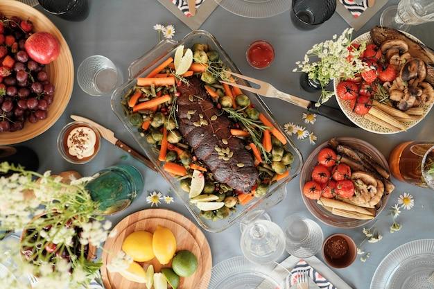 Высокий угол обзора мяса с овощами и других вкусных блюд на столе, приготовленном для праздничного ужина