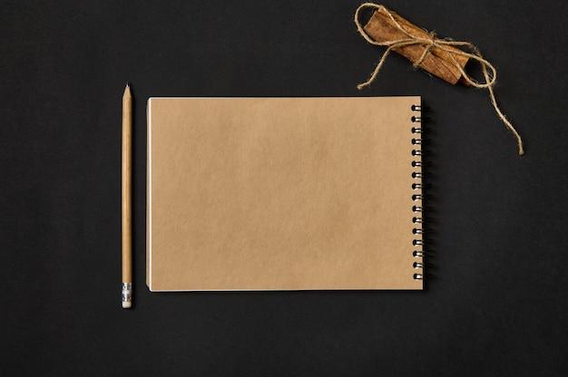 コピースペース、木製の鉛筆、黒の背景にロープで結ばれたシナモンと空の白紙のシートとクラフトノートのミニマルな構成の高角度ビュー