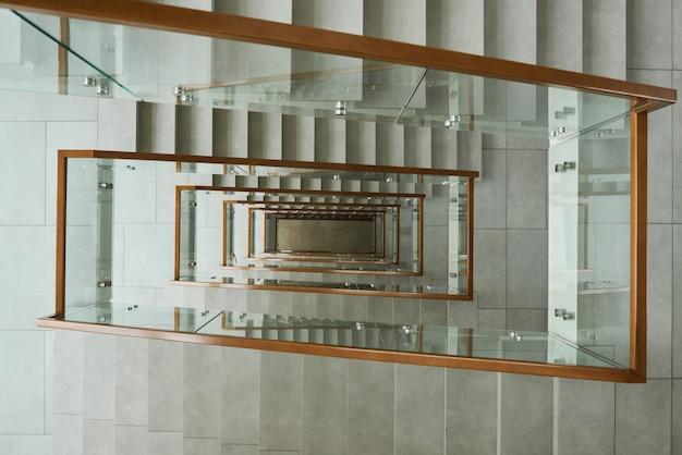 건물에 유리 난간이 있는 현대적인 계단의 높은 각도 보기