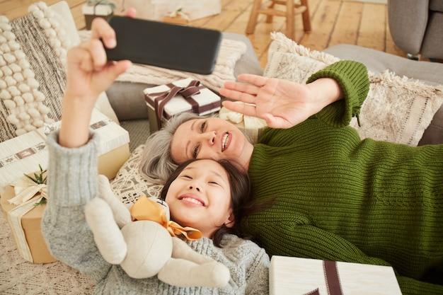 携帯電話を使用してオンラインで話している間、手を振って笑っている母と娘の高角度ビュー