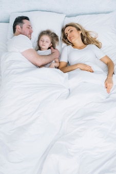 Высокий угол зрения матери; дочь и отец отдыхают на белой кровати