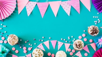 High angle view of muffins with party accessories on green surface
