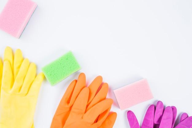 Высокий угол зрения разноцветных перчаток и губки на белом фоне