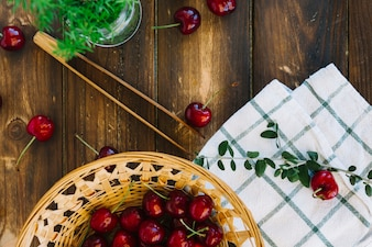High angle view of napkin and red cherries in wicker bowl