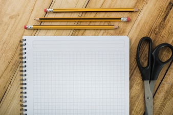 High angle view of notepad; scissors and pencils on wooden backdrop