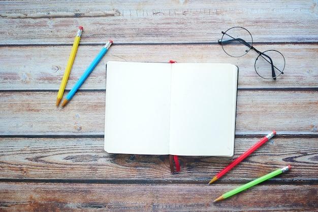 탁자에 있는 열린 일기와 다채로운 연필의 높은 각도 보기