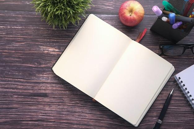 Высокий угол обзора открытых пустых книг и яблоко на столе