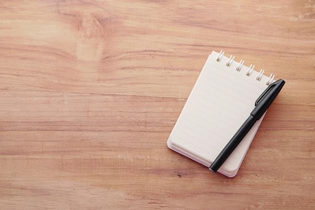 黒の背景に開いているメモ帳の高角度ビュー