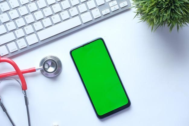 Высокий угол обзора таблеток, смартфона и стетоскопа на столе в клинике