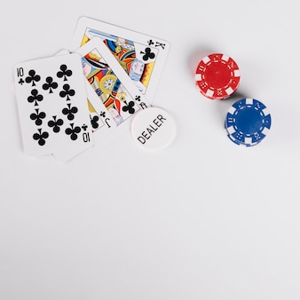 High angle view of playing cards with dealer and casio chips