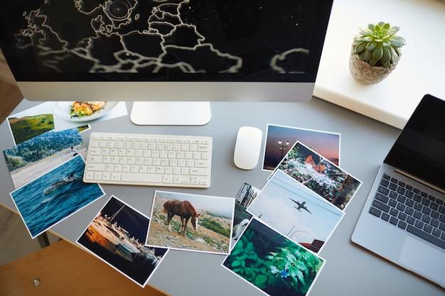 Высокий угол обзора профессиональных фотографий с монитора компьютера на рабочем месте дизайнера в офисе